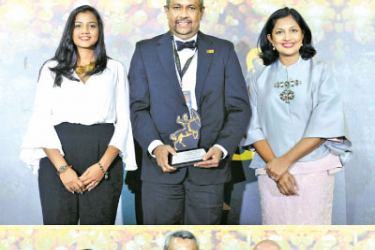 Commercial Bank's Chief Risk Officer Kapila Hettihamu with the two ACES awards presented to the Bank in Singapore.