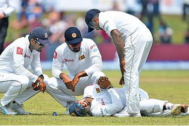 Asela Gunaratne lies hurt on the field after injuring his left thumb during the first Test against India at Galle in July.