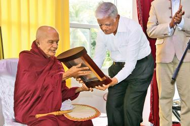 Ven. Kudaheelay Pagnasekera presenting the plaque to H. B. Gunasena. Picture by Priyan De Silva.