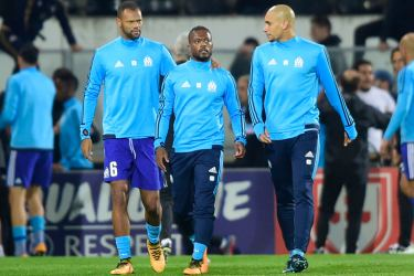 Marseille's French defender Patrice Evra (C) is escorted off the pitch by teammates Portuguese defender Rolando and Brazilian defender Doria after an argument with supporters before the start of the UEFA Europa League group I football match Vitoria SC vs Marseille on November 2. AFP