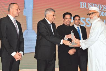 """Prime Minister Ranil Wickremesinghe presenting the """"Passionate 2017' Award to N.L.M. Mubarack at the Awards ceremony."""
