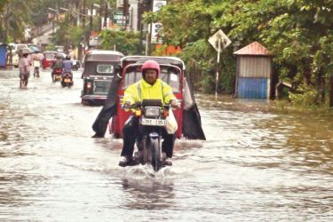 Strong winds that blew across the country damaged houses and properties in many parts of the island. Here, motorists trying to negotiate the floodwaters at Dangedara. Picture by T.D. Siriwardena, our Kalutara Roving Corr.
