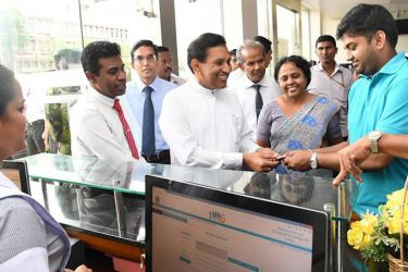 Health Minister Dr. Rajitha Senaratne offers the first e-Health card to a patient at the Sri Lanka National Dental Teaching Hospital in Colombo.