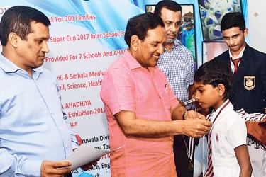 Health Minister Dr. Rajitha Senaratne presenting a medal to a schoolgirl, while State Pharmaceutical Corporation (SPC) Managing Director Dr. Rumi Mohammad looks on.