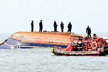 South Korean coastguard members search for missing persons after a fishing boat crashed with a fuel tanker at sea near the western port city of Incheon yesterday.- AFP