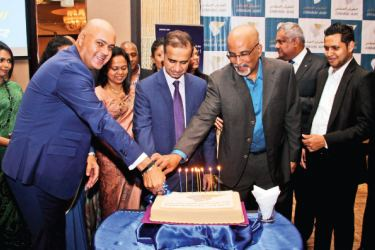 Anniversary cake being cut by Ambassador and the Oman Air team.