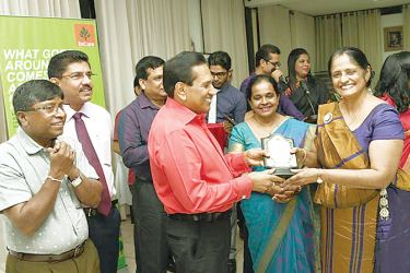 Health Minister Dr. Rajitha Senaratne handing over an award to Dr. Neelamani Hewageeganage, while Health Services Director General Dr. Anil Jasinghe, Dr. Jayasundara Bandara and others look on.