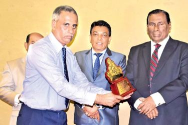 President of Mihimandala Upul Devapriya receiving the award from Minister W.D.J. Senevirathne and the Chairman of British Way English Academy Doctor H.A.S. Geethadewa look on.