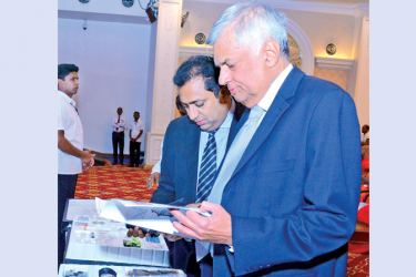Prime Minister Ranil Wickremesinghe inspecting the mobile science laboratory kits to be distributed among 3,000 rural schools, at a function at Temple Trees yesterday. Education Minister Akila Viraj Kariyawasam was also present.  Picture by Hirantha Gunathilaka