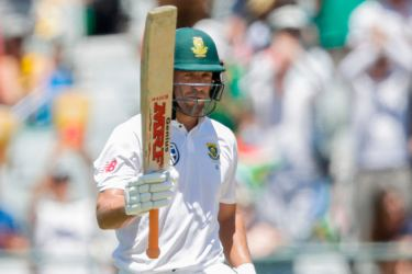 South African batsman AB de Villiers raises his bat as he celebrates scoring a Half-Century during day one of the First Test between South Africa and India in Cape Town, on January 5, AFP