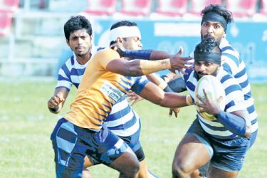 A Navy SC player avoids a tackle from an Army SC defender in their Dialog 'A' division league rugby match played at Havelock Park yesterday. Picture by Wasitha Patabendi