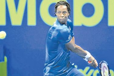 Gael Monfils of France returns to Andrey Rublev of Russia.