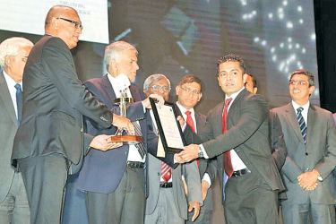Prime Minister Ranil Wickremesinghe presenting the Overall Excellence in Annual Financial Reporting, Silver to officials of Hayleys PLC