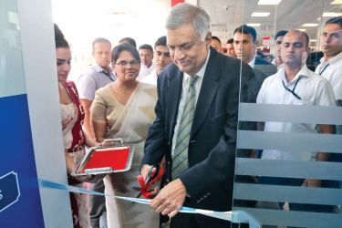 Prime Minister Ranil Wickremesinghe inaugurates Commercial Bank's 756th ATM while the Bank's DGM Personal Banking, Sandra Walgama looks on.