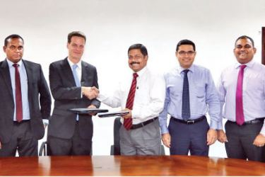 Commercial Bank's Executive Director/Chief Operating Officer, S. Renganathan and Executive Vice President and Commercial Director of INSEE Cement, Jan Kunigk exchanging the agreement in the presence of senior management of the two companies.