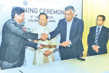 SPMC Chairman Dr. Sayura Samarasundara and the representative of the foreign company shake hands after signing the agreement while Health Minister Dr. Rajitha Senaratne looks on.