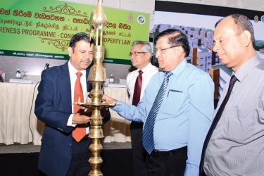 Housing and Construction Ministry Secretary  R. M. Abeyratne and Condominium Management Authority Chairman  C. A. Wijeyeweere lighting the oil lamp, while National Housing Development Authority Chairman L. S. Palansooriya,  Condominium Management Authority General Manager R. K. Jayaweera, and other dignitaries look on.