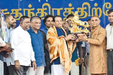 President Maithripala Sirisena is presented with a memento by former provincial minister A.L.M. Athaullah, at the Addalachenai election rally.
