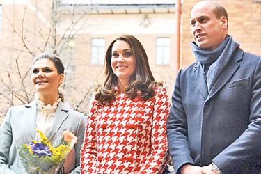 The beaming Duchess poses for a photo with William and Victoria, whose stylish blouse with a pie crust collar could be seen peeking out from beneath her belted suit. She wore her hair in a sleek ponytail and wore a pearl bracelet.