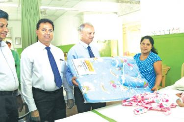 The Chief Executive Officer and General Manager of People's Bank,  N. Vasantha Kumar offering a gift to a newborn baby at the Castle Street Hospital, Borella.