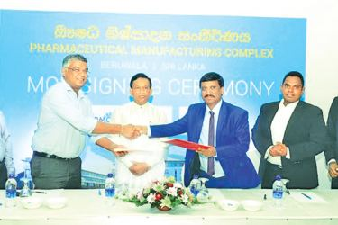 Health Minister Dr Rajitha Senaratne looks on while representatives from the Sri Lankan and Indian firms exchange documents after signing the agreement.