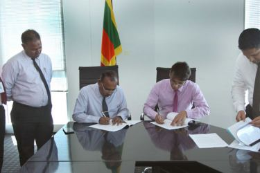 D. N. R. Siriwardena, Registrar General of Companies and R. P. A. Wimalaweera, Commissioner General of Labour signing the MoU.