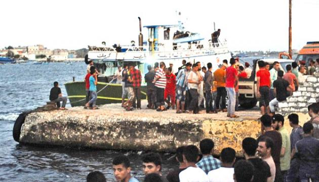 People gather along the shore in the Egyptian port city of Rosett during a search operation after a boat carrying migrants capsized in the Mediterranean. - AFP