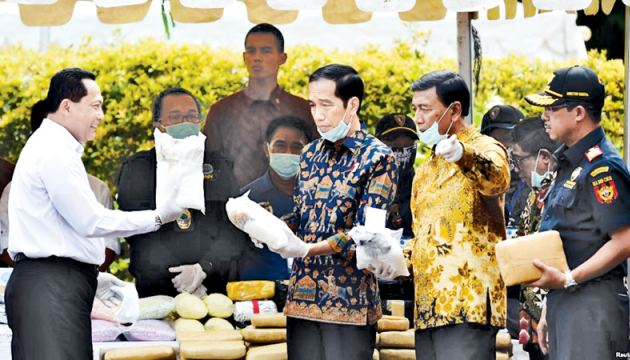 Indonesian President Joko Widodo (C) and other officials prepare to destroy illegal narcotics during an event in Jakarta, Indonesia. - AFP