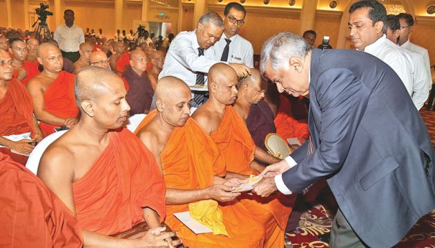 Prime Minister Ranil Wickremesinghe distributing financial assistance among temples