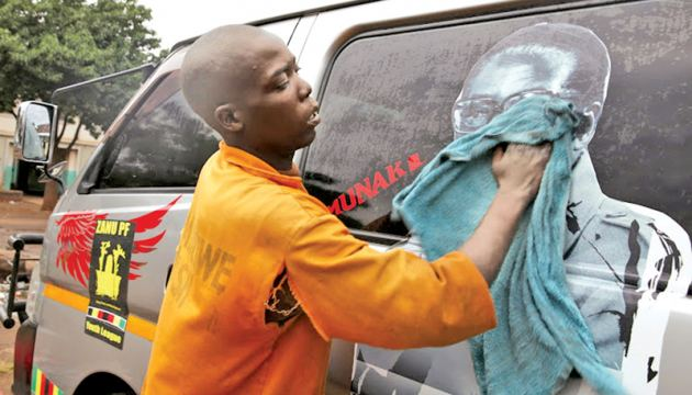 A man washes a minibus adorned with picture of President Robert Mugabe at a bus terminus in -AFP