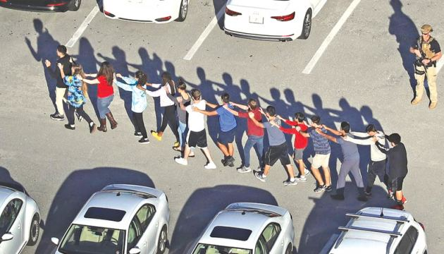 Staff and students are evacuated from Marjory Stoneman Douglas high school after the shooting on Wednesday.