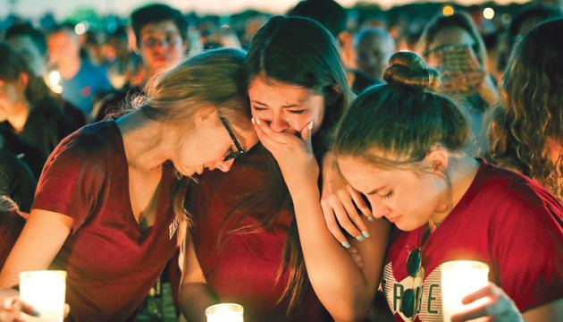 Students console each other as they weep during a candlelight vigil on Thursday for the victims of the shooting at Marjory Stoneman Douglas High School, in Parkland, Florida.