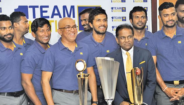 Happy smiles all round as the victorious Sri Lanka team led by Dinesh Chandimal and coached by Chandika Hathurusingha pose with the three trophies they won in Bangladesh with SLC president Thilanga Sumathipala at the SLC headquarters yesterday. Sri Lanka won the one-day tri-series and beat Bangladesh in the Test (1-0) and T20I (2-0) series. Picture by Rukmal Gamage