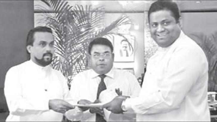 Constructions, Engineering Services, Housing and Common Amenities Minister Wimal Weerawansa, donating a 60 perch land belonging to the Sri Lanka State Engineering Corporation (SLSEC), to the Dankotuwa Divisional Secretariat for the construction of the 'Seva Piyasa' building. Here MP Arundika Fernando receives the deed of the land from Minister Weerawansa..