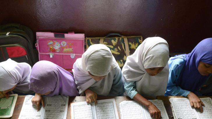 Muslim girls reciting the Holy Quran. AFP