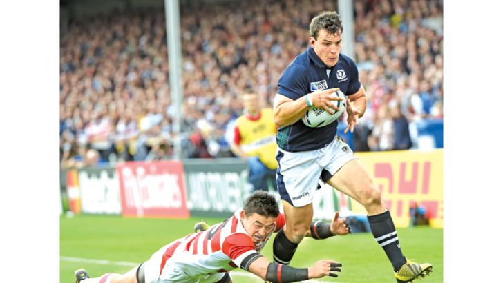 Scotlands John Hardie (R) runs wth the ball as he sets up his try during a Pool B match of the 2015 Rugby World Cup between Scotland and Japan at Kingsholm stadium in Gloucester, west England on September 23, 2015.  AFP