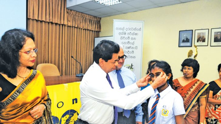 Health Services Director General Dr. Palitha Mahipala helps a child to wear a new pair of spectacles while others look on.