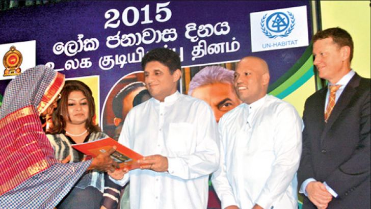 Minister Premadasa granting an ownership deed to a recipient. Picture by Kelum Liyanage