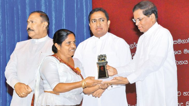 President Maithripala Sirisena hands over a memento to a teacher at the International Teachers' Day celebrations held at the BMICH, yesterday. Picture by Wasitha Patabendige