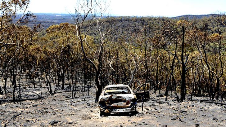 A charred car stands destroyed after a bushfire moved through the area near One Tree Hill in the Adelaide Hills. - AFP