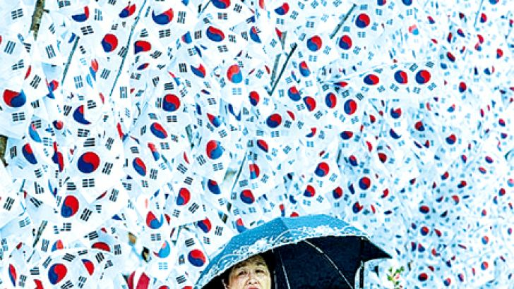 A South Korean woman walks by national flags in Seoul to celebrate the 70th anniversary of Independence Day in August. South Korea was liberated from Japan's 35-year colonial rule on August 15, 1945 at the end of World War II.