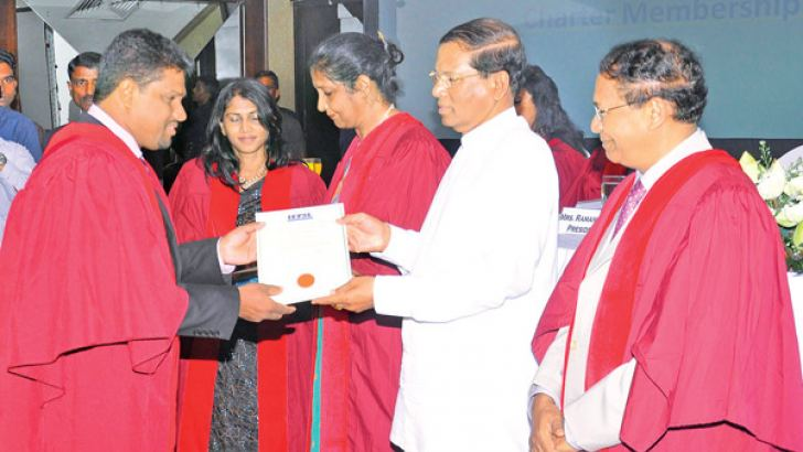 President Maithripala Sirisena handing over Charter Memberships to qualified and experienced environmental professionals, who have made significant contribution to the field. The President awarded Charter Membership to Dr. Ajith Gunawardene as a mark of appreciation for his significant contribution to the environment sector. Picture by Sudath Malaweera