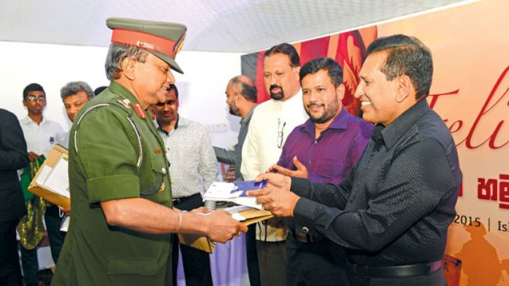 Health, Nutrition and Indigenous Medicine Minister Dr. Rajitha Senaratne hands over a token of appreciation to Major General Ubhaya Medawela while Industry and Commerce Minister Rishad Bathiudeen and others look on. Picture by Health Ministry Media Unit