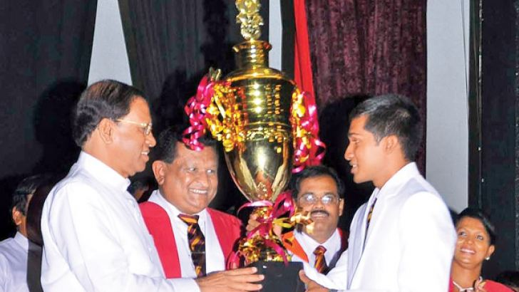 President Maithripala Sirisena was chief guest at the annual prize giving of Ananda College, Colombo, held at the School auditorium on Monday. Picture shows the President presenting an award to Lahiru Ambewela who was named the Student of the Year. Principal Kithsiri Liyanagamage and Minister Arjuna Ranatunga, an old boy of the college are also in picture. Picture by Sudath Malaweera