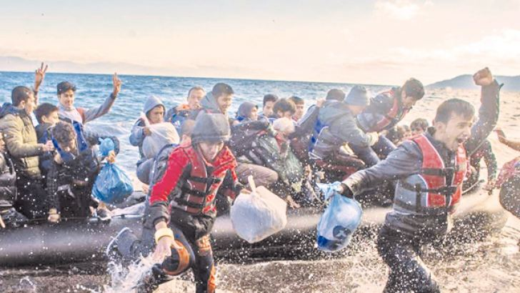 Jubilant refugees embark from a dinghy on the shores on Lesbos.