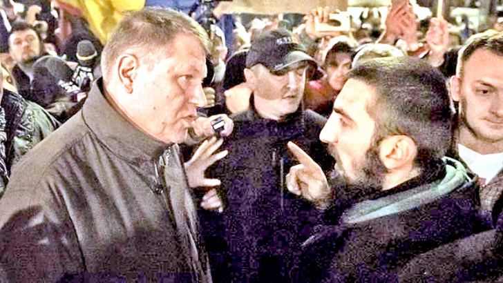 Romanian President Klaus Iohannis (L) speaks to a protester in University Square, Bucharest, the staging area for protests calling for better governance and an end to corruption.- AFP