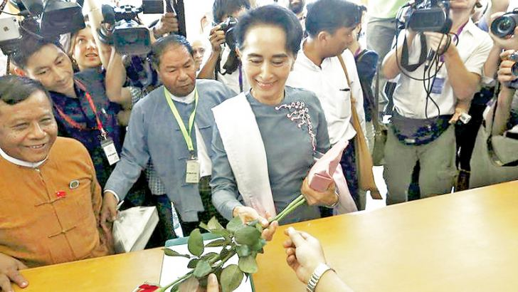 National League for Democracy (NLD) party leader Aung San Suu Kyi receives roses as she arrives for Myanmar's first Parliament meeting after the November 8 General Election, at the Lower House of Parliament in Naypyitaw yesterday. - AFP