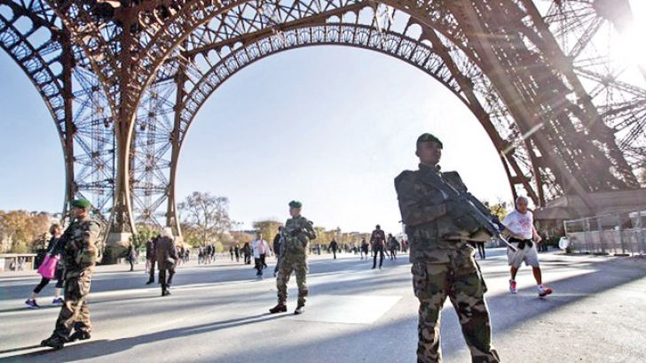 Members of the French army walk on patrol through the base of the Eiffel Tower in Paris.