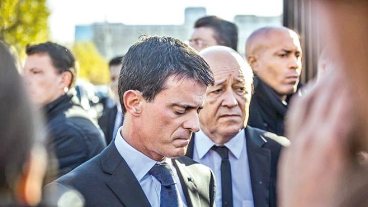 French Prime Minister Manuel Valls (L) and French Defence Minister Jean-Yves Le Drian react as they speak to journalists after visiting those injured in last Friday's terrorist attacks.- AFP