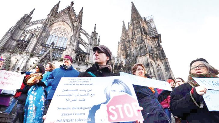 """A  woman holds a sign reading """"Sexual harassment against women will not be  tolerated"""" during a demonstration in front of the cathedral in Cologne  on January 9.- AFP"""